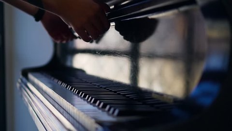 Close up shot of a artist opening a white piano
