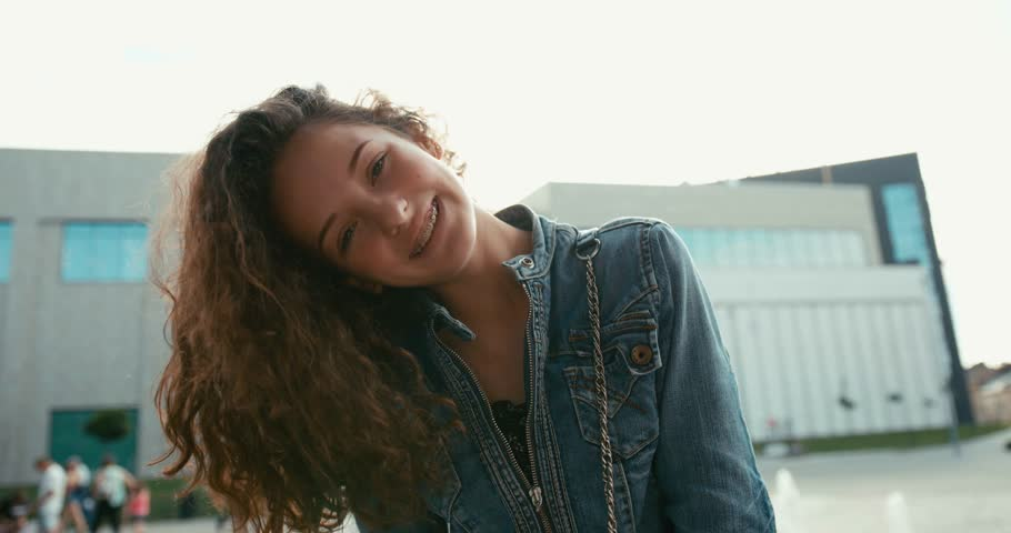 Emotional portrait of the lovely smiling girl with braces on her teeth actively shaking her dark curly hair outdoor. | Shutterstock HD Video #1013361605