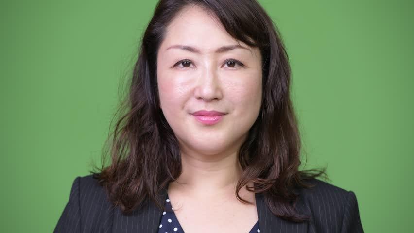 Mature beautiful Asian businesswoman against green background | Shutterstock HD Video #1013379455