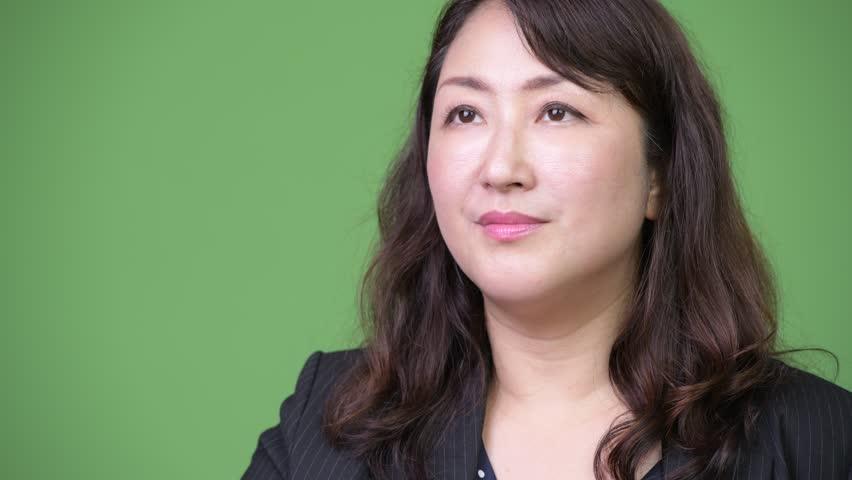 Mature beautiful Asian businesswoman looking shocked | Shutterstock HD Video #1013382095