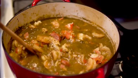 Hand stirs chunky gumbo with wooden spoon, Closeup