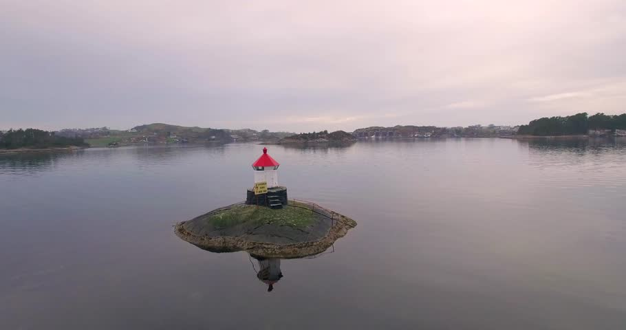 4k: Orbitig smal light house on smal islet with drone. Soft colors.