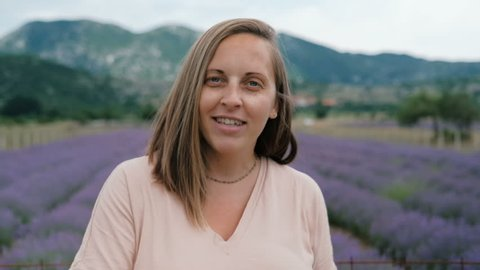 Pretty young woman talking at camera at lavender field.