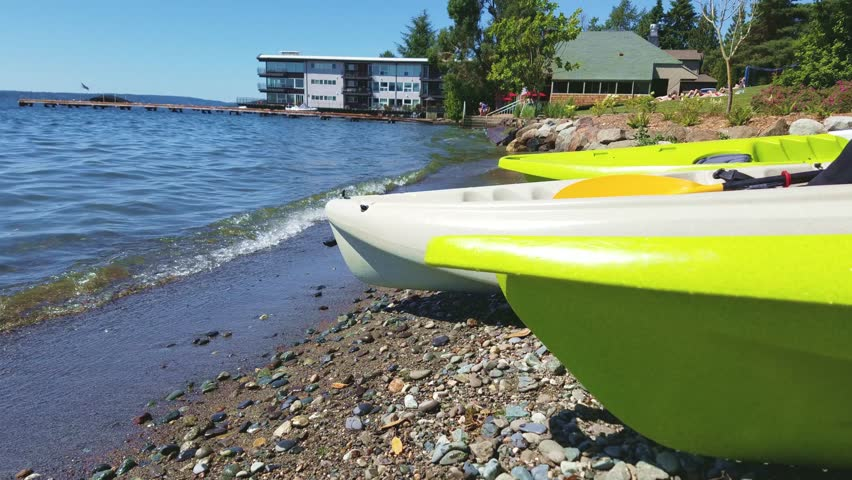 Three kayaks in closeup laying by the seashore during summer, side view closeup