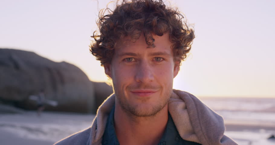 Portrait of attractive man smiling on beach at sunset in slow motion RED DRAGON | Shutterstock HD Video #10134215