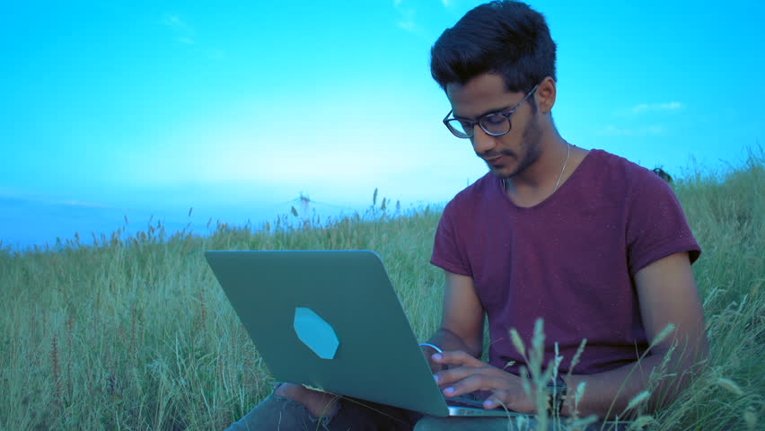 Indian Guy in Glasses Works behind a Laptop Sitting on the Grass on the Hill Top At The Sunset of the Day