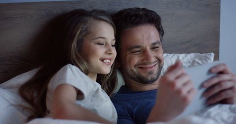Close up of the cheerful father and his small daughter lying in the bed before falling asleep and smiling while watching funny video on the smartphone. Indoors.