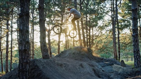 BMX rider doing a tailwhip on a trail jump set in the woods