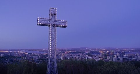 AERIAL: Flying over the cross structure in a forest at night on Mont Royal, It overlooks the city of Montreal, Canada