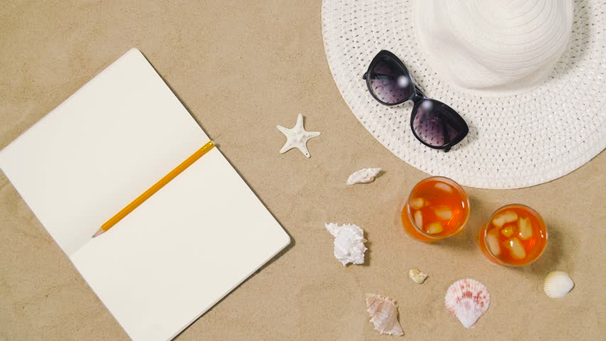 vacation, travel and summer concept - notebook with pencil, two glasses of aperitif cocktails, sun hat and sunglasses on beach sand