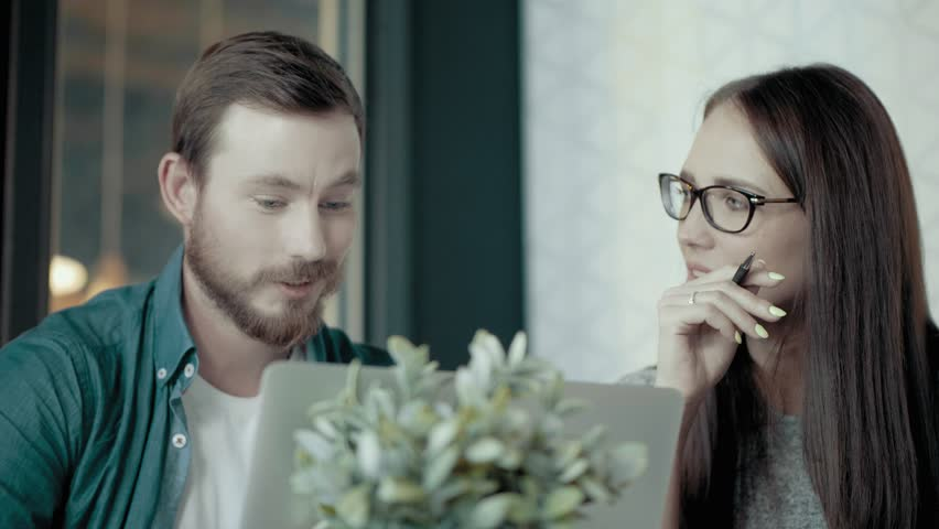 Thoughtful female team leader in glasses and european male programmer discuss developing and promoting new mobile application use laptop people group teamwork in modern start up office slow motion   Shutterstock HD Video #1013484965