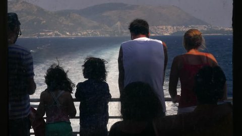 Rear shot from a family standing together at the end of a ship looking at the sea and V shaped pattern of Kelvin wake