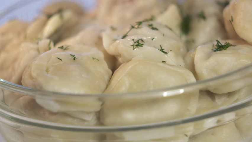 Bowl of homemade boiled dumplings with butter rotating inside microwave. Traditional Russian dish pelmeni filled with meat.