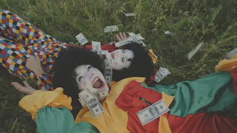 Two cheerful clowns lay on the grass in the field under falling dolars. 4K