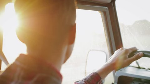 This is close up type portrait footage of young car driver driving jeep during sunset. You can see golden hour light on his face.
