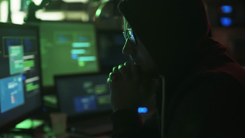 Nerd hacker with hoodie working at desk late at night, he is watching multiple screens and hacking networks, cyber security concept | Shutterstock HD Video #1013574425