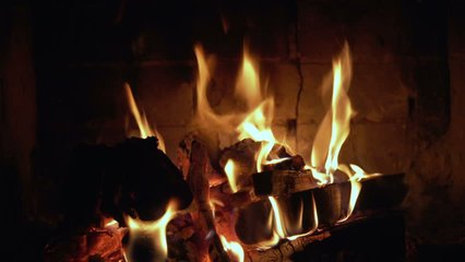 A fireplace with a hot roaring fire and red coals. A looping clip of a fireplace with medium size flames