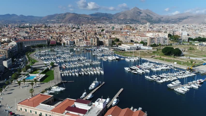 Aerial footage of marina yacht club located at Palermo Sicily Italy showing streets on left and harbor on right furthermore showing the city center and mountains in background 4k high resolution