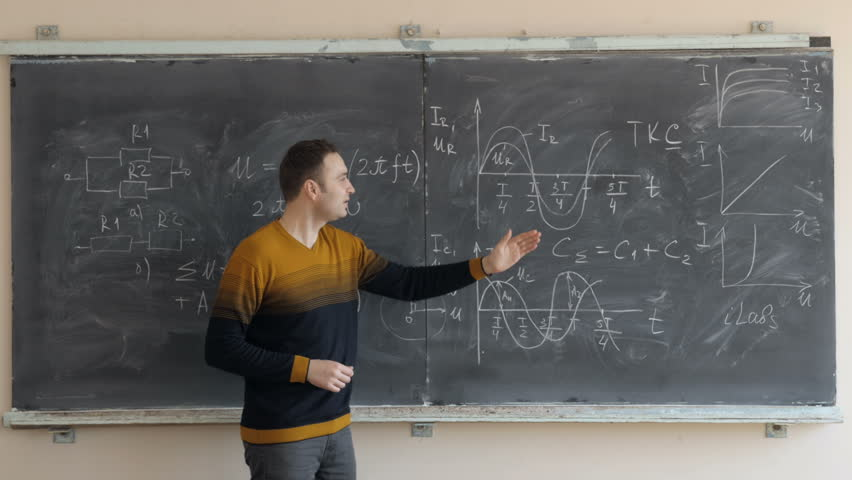 Young teacher or student explaining schemes and graphics near the blackboard  | Shutterstock HD Video #1013598845