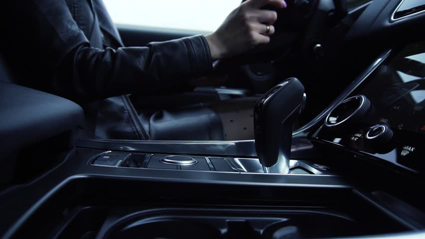 Business woman uses transmission. Stock. Female hand on automatic transmission car lever