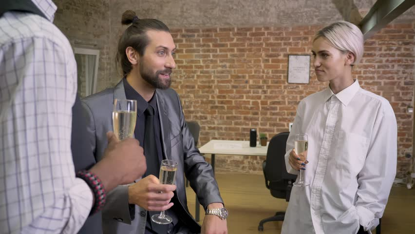 Three multy-ethnic workers tell stories, body language, sitting in office, drinking champagne, communication concept | Shutterstock HD Video #1013617085