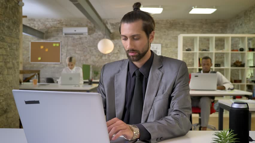 Handsome businesswoman with beard is typing on laptop in office, watching at camera, smiling, colleagues are networking with technologies, work concept, communication concept | Shutterstock HD Video #1013617115