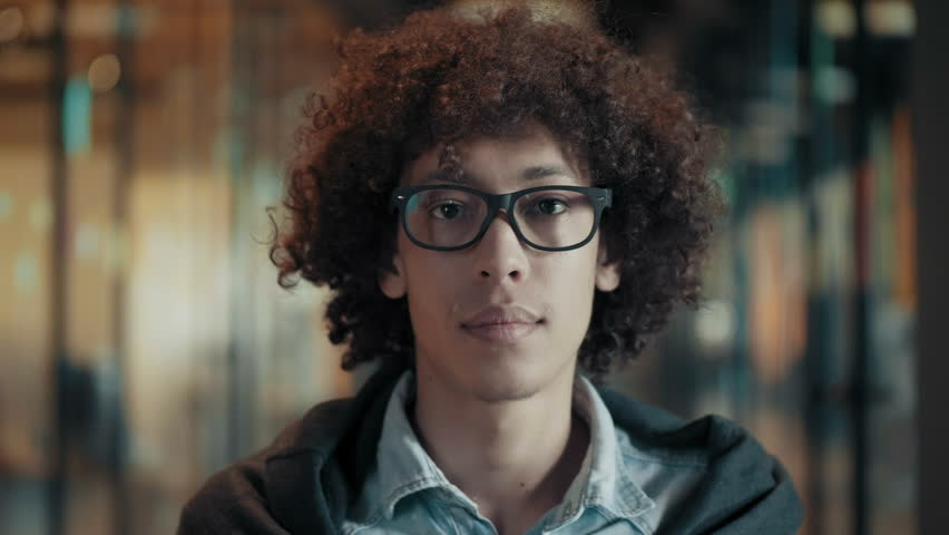 Close up face of tranquil calm african young male in glasses black guy with dark curly hair portrait of creative young man in stylish clothes in modern start up office quietly watching and blinking | Shutterstock HD Video #1013618225