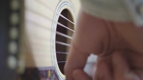 Guitar player strumming a nice rhythm, Close up in Slow motion.
