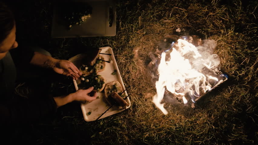 Camp fire during the night with some bacon roasting | Shutterstock HD Video #1013648915