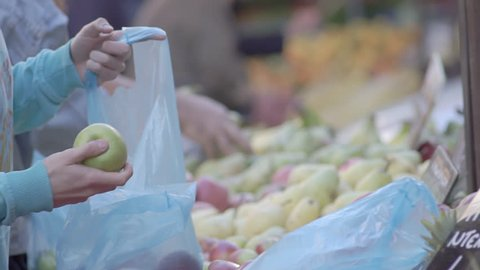 Slow Motion Shot Of Male And Female Customers Hands Choosing Green Apples And Bagging Them Into Blue Plastic Bags At A Street Fruit Market Stall, Supplying Plastic Carrying Bags To Customers.