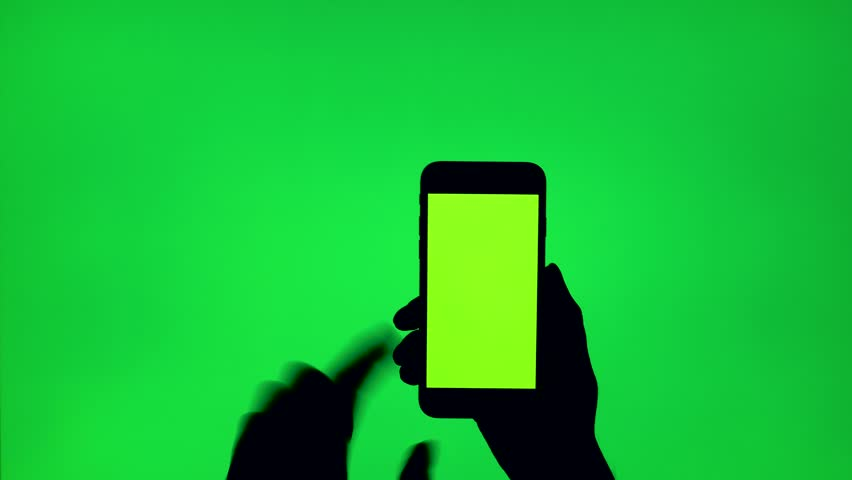 Close-up on the silhouette of a woman's hand making different random gestures with a mobile phone, greenscreen background, shoot in 4K | Shutterstock HD Video #1013669345