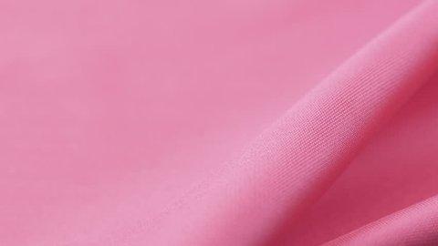 Closeup of pink satin fabric texture. Dolly shot