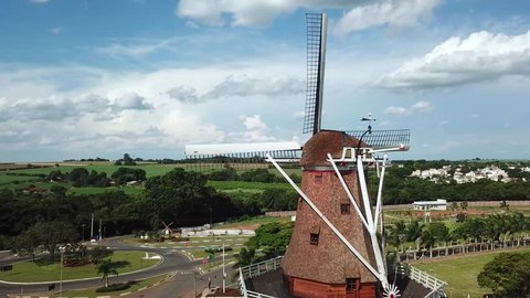 Flying around a windmill in green fields, aerial shot