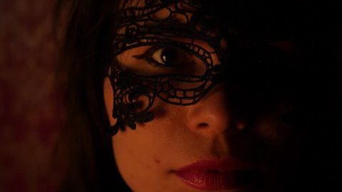 mysterious woman in a black, openwork mask