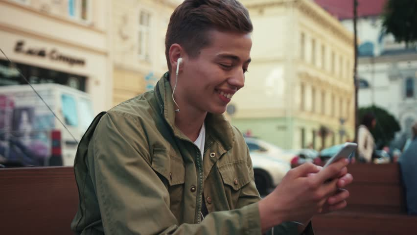 Face young man use phone listen music in headphone sitting on street smile feel happy cell sunlight walking mobile gadget technology handsome hipster close up slow motion portrait | Shutterstock HD Video #1013720885