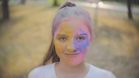Portrait of a cute girl painted in the colors of Holi festival.