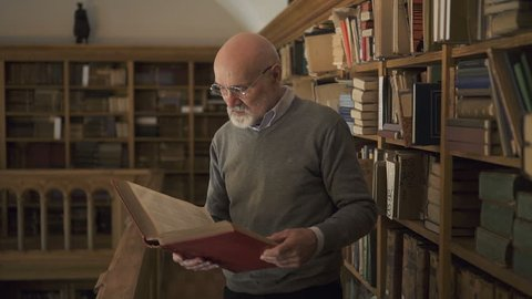 Mature male researcher in glasses standing near the bookshelves in the library, holding a book in his hands, looking to the camera and smiling. Indoors. Portrait.