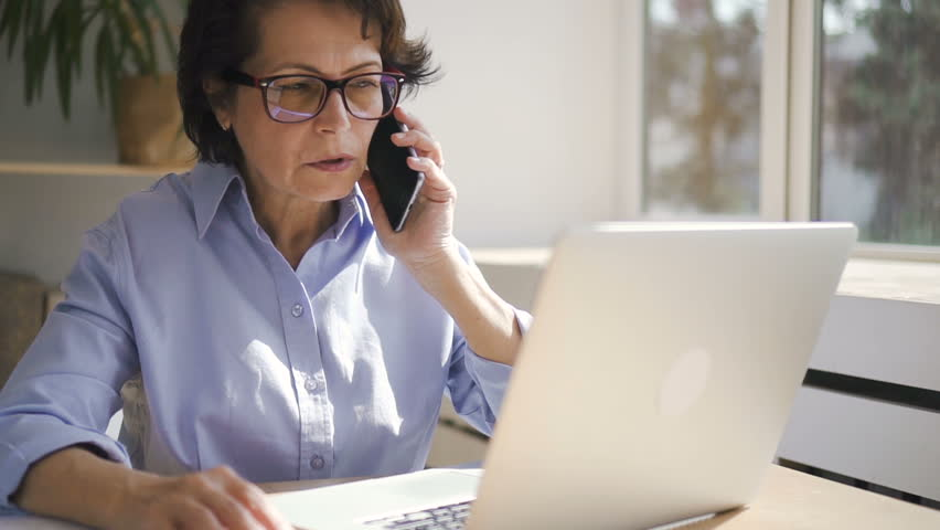 Senior businesswoman in glasses and blue shirt working on brand-new laptop and taking on phone near the window in cozy office with plants on the background. | Shutterstock HD Video #1013757095