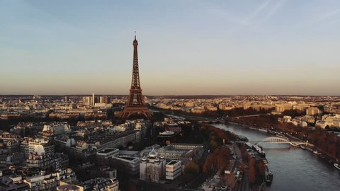 Aerial shot of Paris with the Eiffel tower and the Seine in the center. The surrounding buildings are painted in orange light by the rising sun.