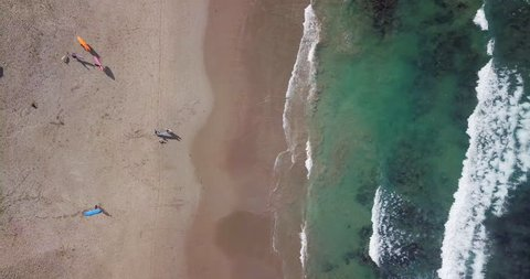 Aerial top view waves break on sand beach at sunset. Sea waves on the beautiful beach aerial view drone 4k shot. Bird's eye view of ocean waves and sporty surfers with surfing boards from above.