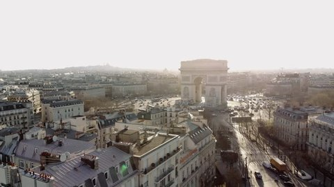Sunny morning in Paris. A wide aerial shot shows the Arc de Triomphe and the Champs Elysees in golden morning light. The camera sinks into a small park in Avenue Foch.