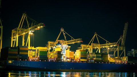 Close up of huge cargo container ship in the dock unloading by the big industrial crane on black background