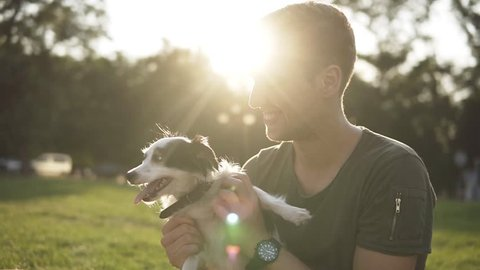 Man sits on the grass in the green park, play with young little dog. Owner tease doggy, play and hug. Smiling, happy owner having fun with his pet. Slow motion