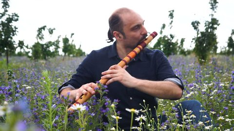 young man playing on flute at summer time outdoor