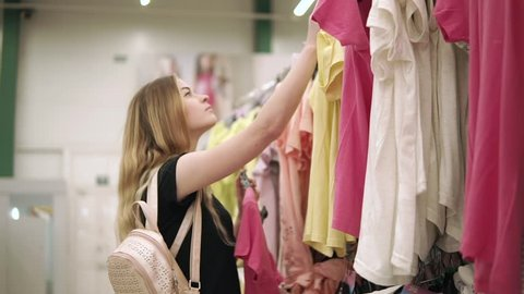 Young blonde woman is holding hanger with clothing in hand and changing it place with other. She is deciding to take other color of shirt in clothing store