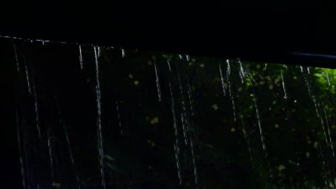 Heavy raining in tropical country ,water from roof dropping down ,low angle view. Raindrops from roof