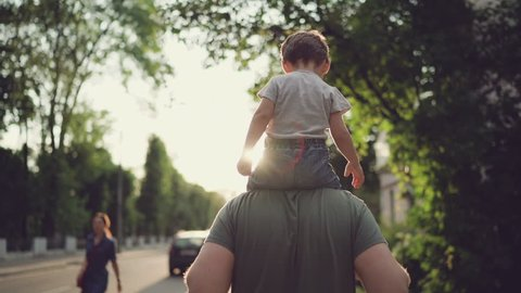 Father and son walking in city at sunset. Two year old kid is sitting on the parent's shoulders. Happy family concept. Footage in slow motion