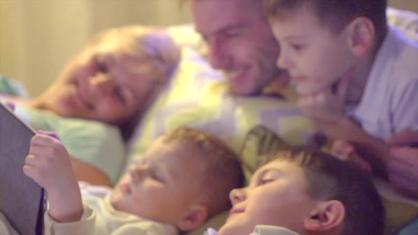 Happy family Father, Mother and three kids lying down on the sofa and using tablet pc at night. Big Family together watching movie on tablet computer in dark room. UHD, slow motion 240 fps, 4K video | Shutterstock HD Video #1013815775