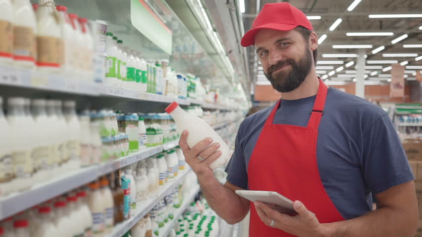 Smiling supermarket employee checking the quality of the milk | Shutterstock HD Video #1013816435