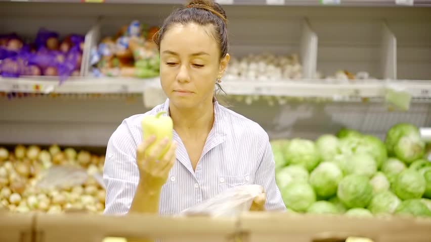 Pretty housewife is smelling yellow paprika in a supermarket and folding in a plastic pack | Shutterstock HD Video #1013819105